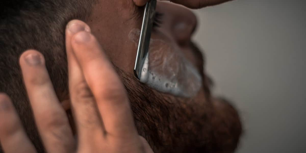 Person shaving himself without the best men's electric razor for sensitive skin